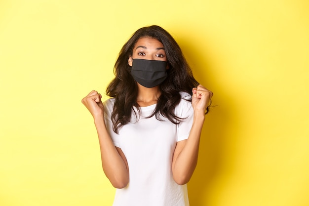 Konzept von covid-19, sozialer distanzierung und lebensstil. fröhliche afroamerikanische frau, die eine schwarze gesichtsmaske trägt, sich mit faustpumpen freut und lächelt, einen preis gewinnt, gelber hintergrund.