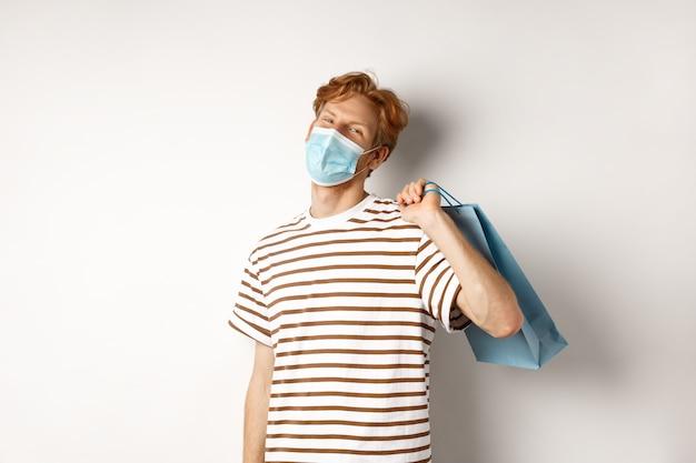 Konzept von covid-19 und einkaufen. zufriedener junger mann, der erfreut nach dem einkaufen schaut, gesichtsmaske trägt, papiertüte hält und lächelnd, weißer hintergrund.