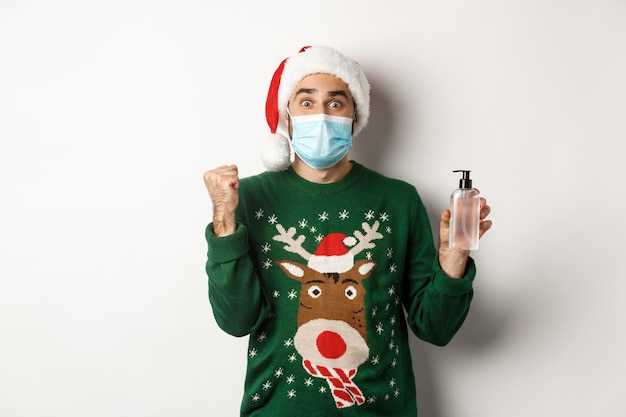 Konzept von covid-19 und weihnachtsferien. fröhlicher mann mit gesichtsmaske, der gutes händedesinfektionsmittel zeigt, weihnachtsmütze trägt und auf weißem hintergrund steht