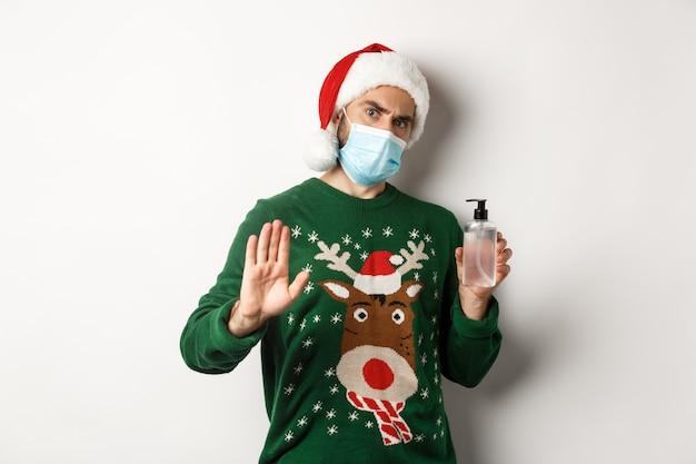 Konzept von covid-19 und weihnachtsferien. mann mit gesichtsmaske und weihnachtsmütze stoppt die person und bittet darum, händedesinfektionsmittel zu verwenden und steht auf weißem hintergrund