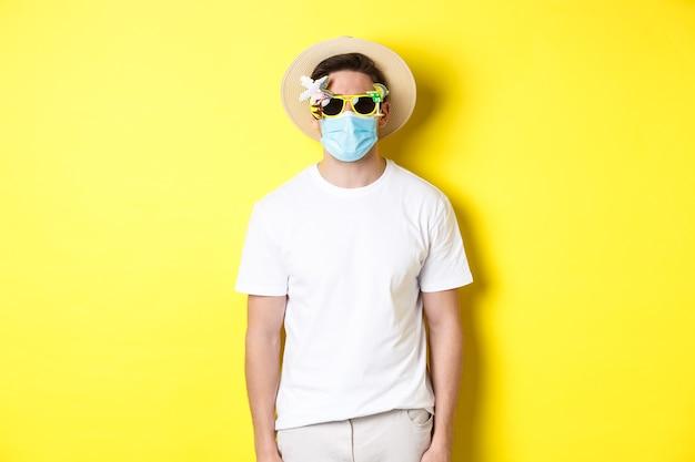 Konzept von covid-19, urlaub und sozialer distanzierung. manntourist, der medizinische maske und sommerhut mit sonnenbrille trägt, auf reisen während der pandemie, gelber hintergrund geht.