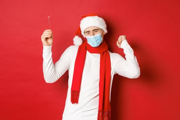 Konzept von covid-weihnachten und feiertagen während der pandemie glücklicher mann, der das neue jahr bei partykleidung feiert...