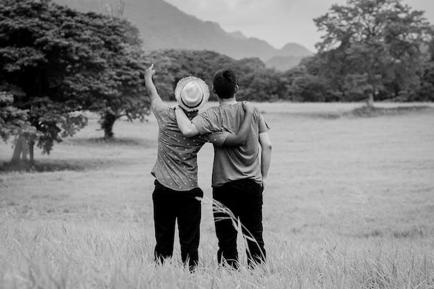 Konzept von den besten freunden, die auf dem feld umarmen schwarzweiss-art
