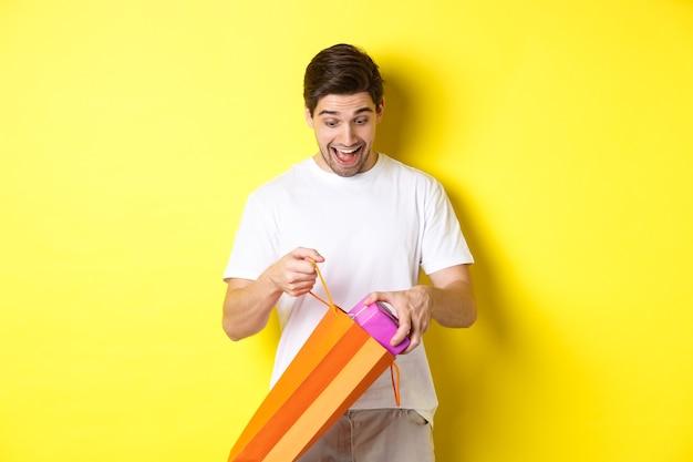 Konzept von feiertagen und feier. junger mann, der als herausnehmendes geschenk von der einkaufstasche überrascht schaut und über gelbem hintergrund steht.