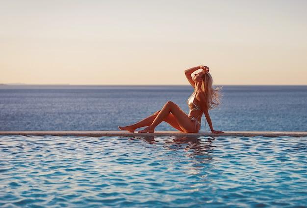 Konzept von ferien durch das meer im pool. mädchen in einem luxuriösen badeanzug am rande eines panorama-pools gegen das meer