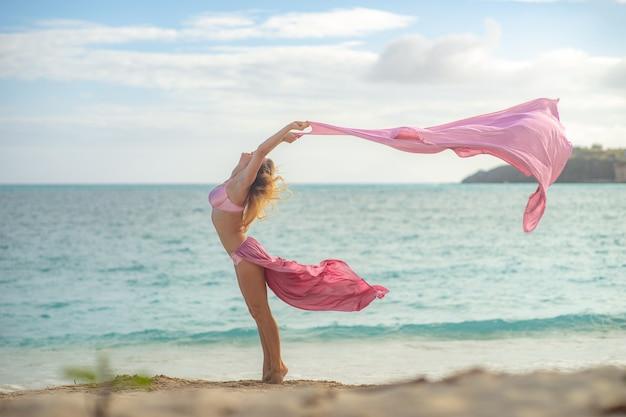 Konzept von freiheit und glück. glückliche frau am strand im sommer mit fliegender rosa seide.
