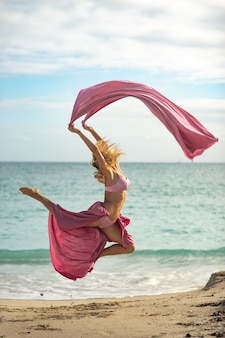 Konzept von freiheit und glück. glückliche frau am strand springend mit fliegender rosa seide.