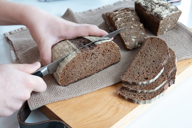 Konzept von hausgemachtem brot, natürlichen landwirtschaftlichen produkten, einheimischer produktion. gesunde und leckere bio-lebensmittel. frau, die frisch gebackenes vollkornbrot schneidet.
