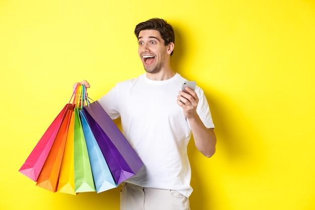 Konzept von mobile banking und cashback. glücklicher mann, der erstaunt schaut, einkaufstaschen und smartphone, gelber hintergrund hält.