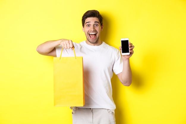 Konzept von mobile banking und cashback. junger glücklicher kerl, der einkaufstasche hält und smartphonebildschirm, gelben hintergrund zeigt.