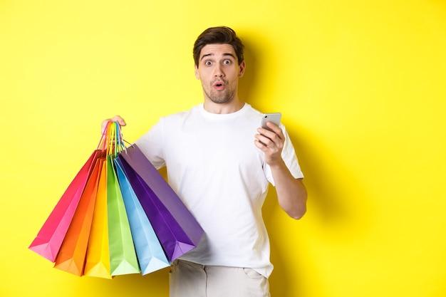 Konzept von mobile banking und cashback. überraschter mann, der einkaufstaschen und smartphone hält, über gelbem hintergrund stehend.