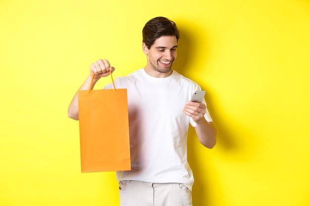 Konzept von rabatten, online-banking und cashback. glücklicher kerl, der einkaufstasche zeigt und zufrieden am mobilen bildschirm, gelber hintergrund schaut.
