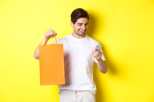 Konzept von rabatten, online-banking und cashback. glücklicher kerl, der einkaufstasche zeigt und zufrieden auf den mobilen bildschirm schaut, gelber hintergrund