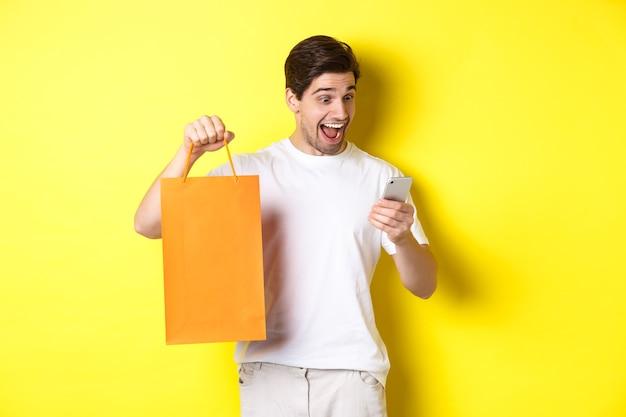 Konzept von rabatten, online-banking und cashback. überraschter mann, der einkaufstasche zeigt und glücklich auf mobilen bildschirm schaut, der gegen gelben hintergrund steht.