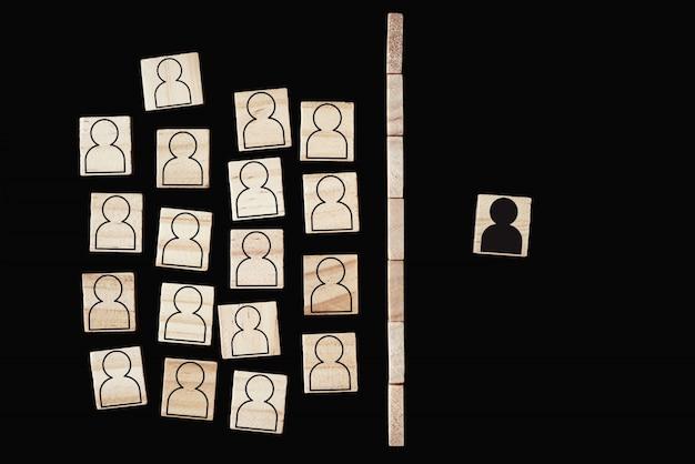 Konzept von rassismus und missverständnissen zwischen menschen, vorurteilen und diskriminierung. holzblock mit weißen personenfiguren und einer mit schwarzem mann