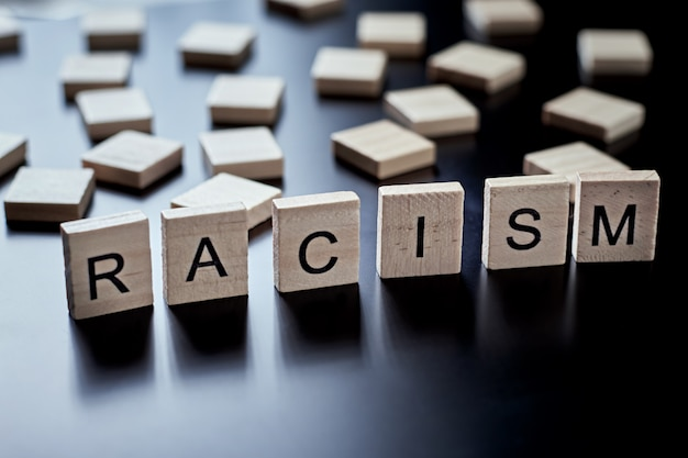 Konzept von rassismus und missverständnissen zwischen menschen, vorurteilen und diskriminierung. holzblock mit wortrassismus auf dem schwarzen hintergrund