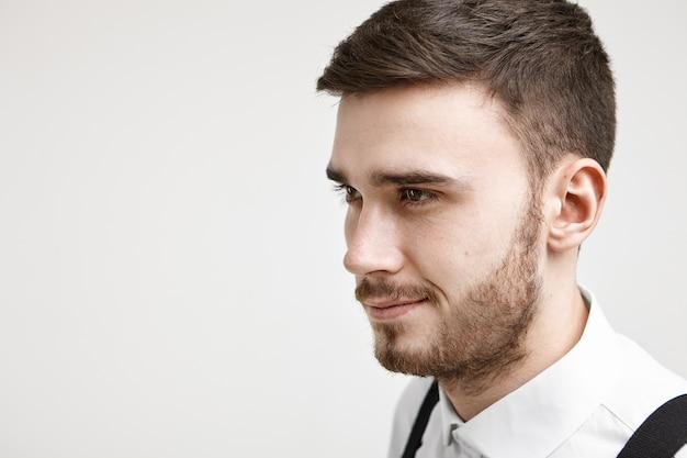 Konzept von selbstvertrauen und männlichkeit. isoliertes studioporträt des positiven selbstbewussten jungen männlichen angestellten mit stilvollem haarschnitt und stoppeln lächelnd, wie er einige große idee bezüglich der arbeit hat