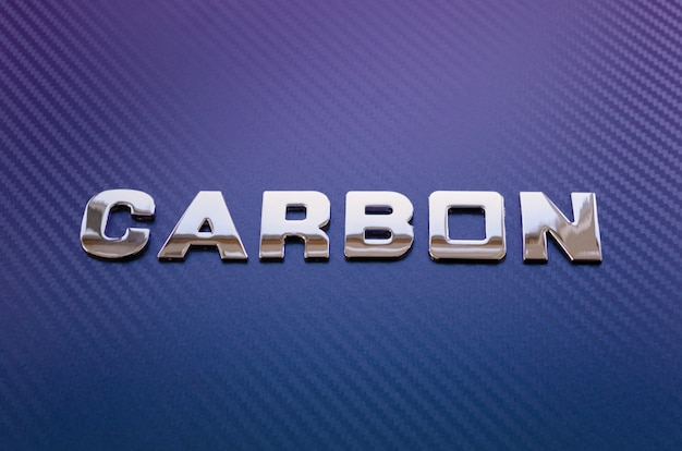 Konzept von sport, geschwindigkeit, rennen und leichtgewicht. wort carbon in chrombuchstaben auf violettblauer kohlefaseroberfläche geschrieben