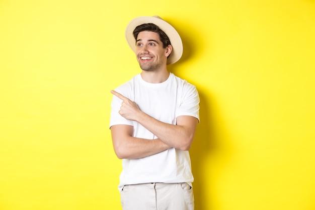 Konzept von tourismus und lebensstil. glücklicher mann tourist, der promo auscheckt, erfreut aussieht und finger auf logo der oberen linken ecke, gelber hintergrund zeigt.