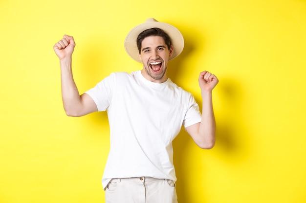 Konzept von tourismus und lebensstil. glücklicher manntourist, der feiert, sich über urlaub freut und über gelbem hintergrund steht.