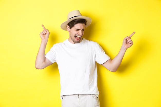 Konzept von tourismus und lifestyle. glücklicher mann, der urlaub genießt, touristischer tanz über gelbem hintergrund.