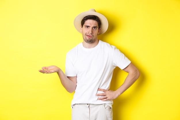 Konzept von tourismus und sommer. junger skeptischer tourist, der sich beschwert, wertend schaut und über gelbem hintergrund steht.
