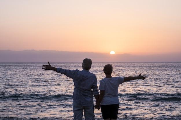 Konzept von urlaub, tourismus, reisen und menschen - glückliches seniorenpaar am kiesstrand lachen und scherzen, das meer bei sonnenuntergang mit ausgestreckten armen beobachten. weißes haar