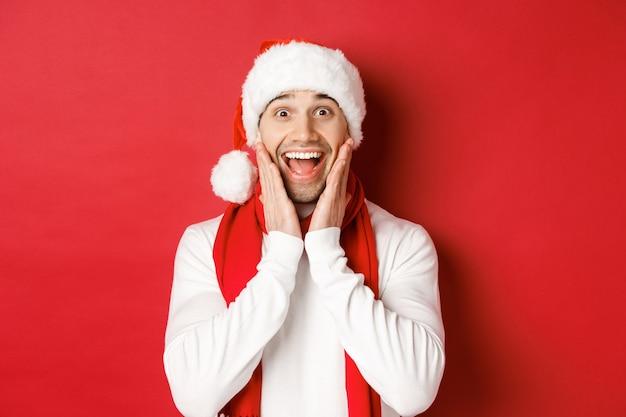 Konzept von weihnachten, winterferien und feier. nahaufnahme eines überraschten und glücklichen mannes in weihnachtsmütze und schal, der etwas erstaunliches betrachtet und über rotem hintergrund steht.
