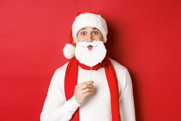 Konzept von weihnachten, winterferien und feier. porträt eines lustigen mannes in weihnachtsmütze, bartmaske haltend, neujahrsparty genießend, über rotem hintergrund stehend