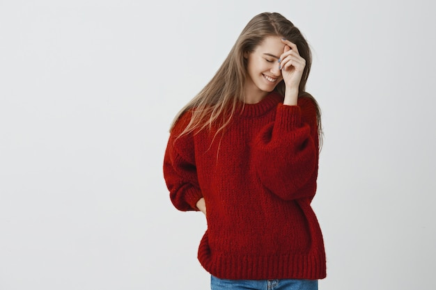 Konzept von zärtlichkeit, schönheit und emotionen. charmante schüchterne junge frau in rotem, lockerem, stilvollem pullover, der flirtend nach unten schaut und süß errötet, als würde er einen blick scheuen, der vor der kamera aufwirft