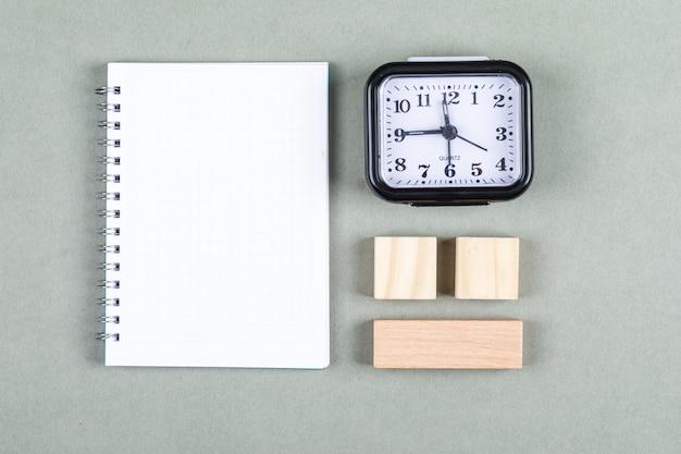 Konzept von zeitmanagement und brainstorming. mit uhr, notizbuch, holzklötzen auf grauer hintergrundansicht von oben. horizontales bild