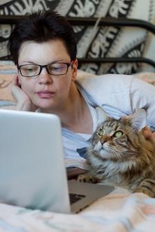 Konzept von zu hause bleiben und sicher bleiben, frau und maine coon katze liegen im bett und arbeiten am laptop, selektiver fokus