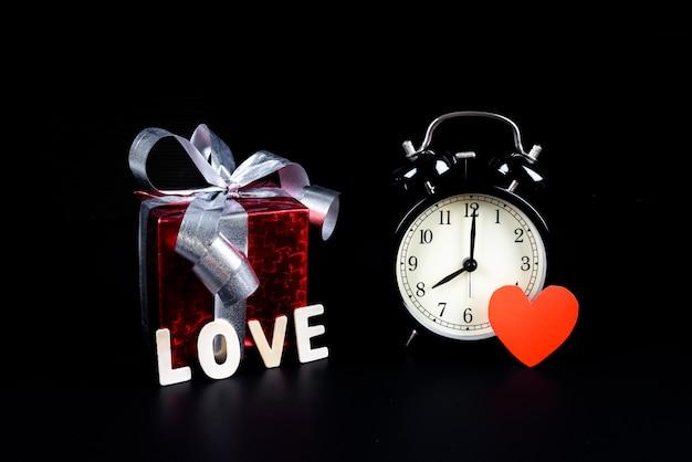 Konzept-wecker des valentinstags mit geschenkbox und hölzernen buchstaben fassen ab