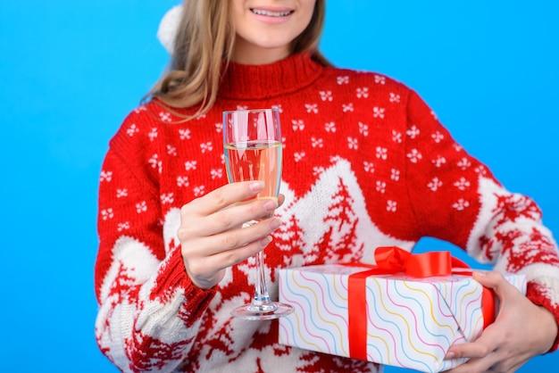 Konzept weihnachtsfeier. geschnittenes nahaufnahmefoto eines glases champagner in der hand der frau. lächelnde schöne frau im gestrickten roten pullover ist auf dem hintergrund