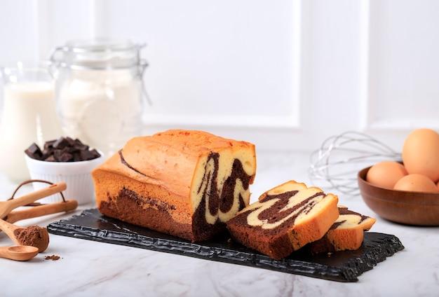 Konzept-weißer hintergrund-bäckerei, laib-marmor-kuchen-scheibe auf steinschwarzplatte mit zutat im hintergrund