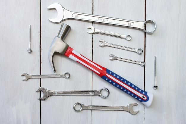Konzept-werkzeugtechniker des glücklichen werktags vereinigter staaten gesetzt auf einen weißen bretterboden.
