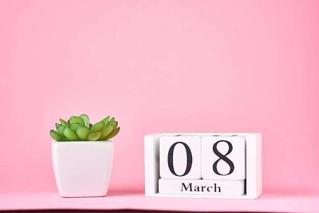 Konzept zum frauentag. hölzerner kalenderblock mit datum 8. märz und pflanze auf rosa mit kopienraum