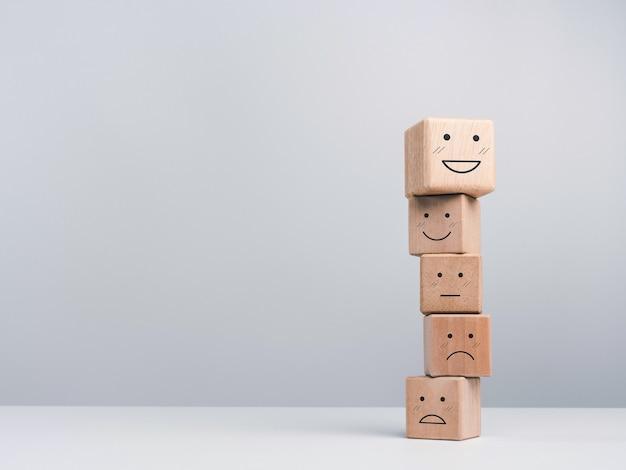 Konzept zur bewertung des kundenservice, feedback und zufriedenheitsumfrage. ein netter glücklicher lächelnder emoticon-holzwürfelblöcke, die auf anderen gefühlgesichtern auf weißem hintergrund mit kopienraum stapeln.
