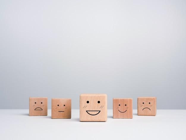 Konzept zur bewertung des kundenservice, feedback und zufriedenheitsumfrage. holzwürfelblöcke mit einem süßen smiley-emoticon mit emotionsgesichtern auf weißem hintergrund mit kopierraum.