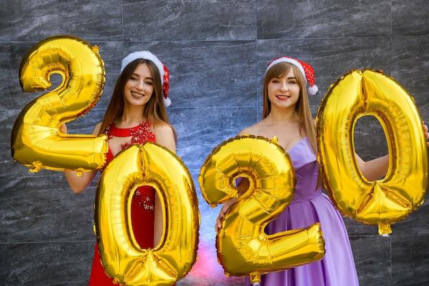 Konzept zur feier des neuen jahres. zwei schöne frauen mit goldenen luftballons 2020