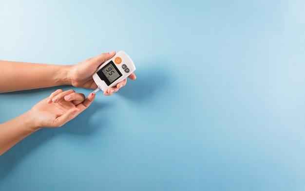 Konzept zur sensibilisierung für den weltdiabetestag. der diabetiker misst den glukosespiegel im blut