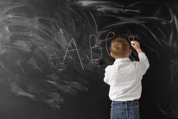 Konzept zurück in die schule. kleiner junge schreibt mit kreide an eine tafel. die ersten buchstaben des alphabets.