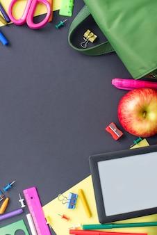 Konzept zurück zu schulapfel-rucksackbriefpapier auf schwarzem hintergrund.