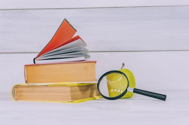 Konzept zurück zur schule. grüner apfel mit lupe auf einem raum der bücher.