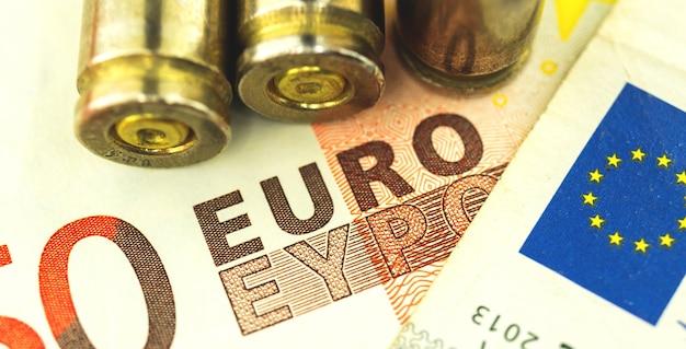 Konzeptbanner für korruption und munitionshandel der europäischen union, krimineller hintergrund mit kugel- und euro-banknoten-nahaufnahmefoto
