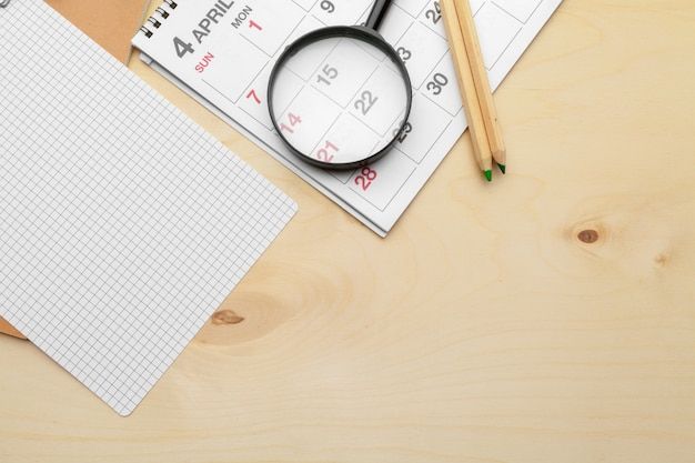 Konzeptbild des geschäfts und der sitzungen. kalender zur erinnerung an einen wichtigen termin und lupe