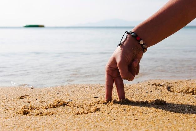 Konzeptbilder - hand in form eines mannes am strand bei sonnenaufgang