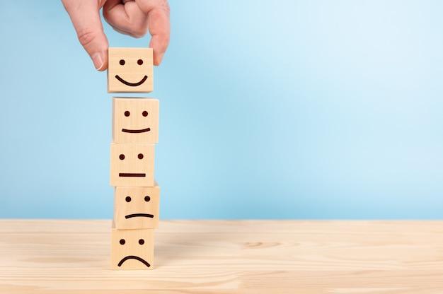 Konzepte zur bewertung des kundenservice und zur zufriedenheitsumfrage. kundenhand wählte glückliches gesicht lächeln gesichtssymbol auf holzklötzen