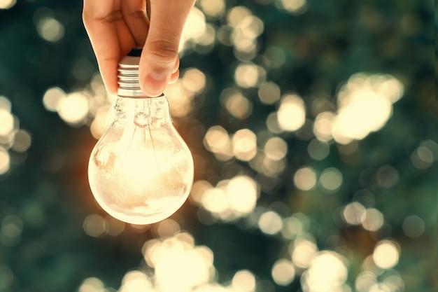 Konzeptenergie in der natur. hand hält glühbirne und sonnenlicht hintergrund