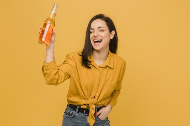 Konzeptfoto der jungen frau trinkt bier und hat etwas spaß beim tanzen
